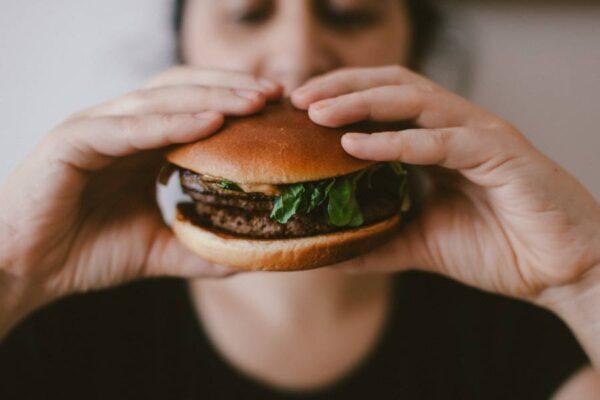 eating comfort food holding burger